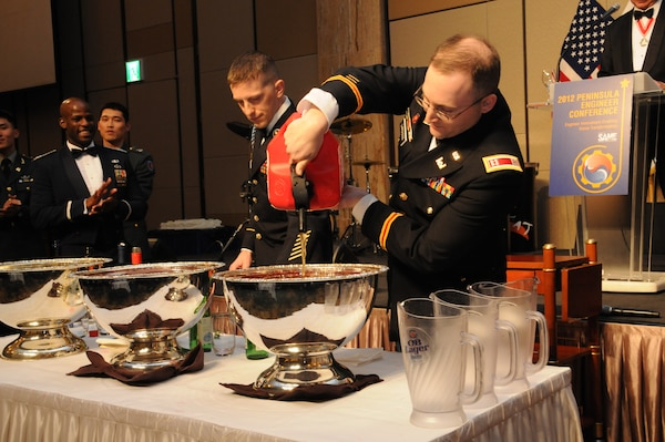 Capt. Matthew Larocco, commander of Company C, 1st Brigade Special Troops Battalion, pours Red Bull into the grog bowl at the Peninsula Engineer Conference Dining Out April 5.