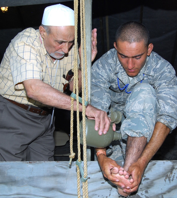 Imam Mohamed Jodeh helps Basic Cadet Wasim Soomro perform wudu prior to evening prayers in the Muslim chapel at Jacks Valley July 22, 2012. Wudu is a form of ablution, or ritual purification, that consists of washing one's hands, feet, mouth and face before praying or touching the Qur'an. Jodeh leads Muslim services as part of the Air Force Academy's lay leader program. (U.S. Air Force photo/Don Branum)