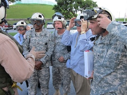 OKINAWA, Japan — Lt. Gen. Thomas Bostick, commanding general of the U.S. Army Corps of Engineers (USACE), Maj. Gen. Kendall P. Cox, USACE deputy commanding general, military and international operations, Gene Ban, USACE director of programs, Pacific Ocean Division, & Col. Bryan P. Truesdell, USACE Japan District commander, receive pre-flight instructions during a visit to the Okinawa Area Office July 18, 2012.