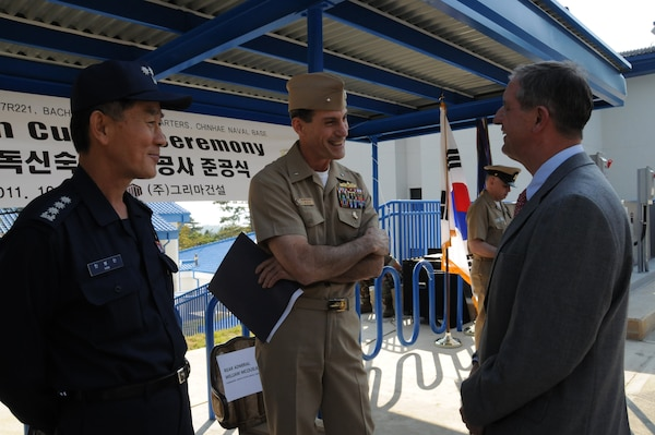 Rear Adm. William McQuilkin (center), Commander U.S. Naval Forces Korea, discusses the new Bachelor Enlisted Quarters at Fleet Activities Chinhae with Sam Adkins (right), Chief of the U.S. Army Corps of Engineers, Far East District Construction Division. Col. Han Bong-wan, Chief of U.S. Forces Korea Construction Management Team, Korea Ministry of National Defense looks on. (Photo by Patrick Bray)