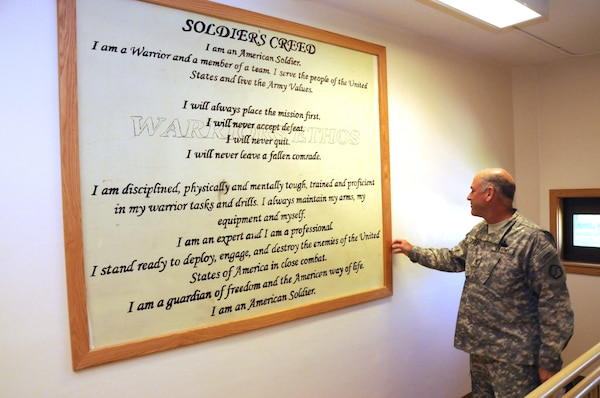 Col. Craig Cutter, Deputy Commander, 19th Expeditionary Sustainment Command, looks over the Soldiers Creed in the stairwell of Daegu High School.  The creed was originally painted on the wall by soldiers when the building was used as a barracks.  The U.S. Army Corps of Engineers, Far East District renovated the barracks to be used as a school.  The mural was intentionally left uncovered to reflect the history of the building and as a symbol of the school's mascot: the Warriors.  (Photo by Patrick Bray)