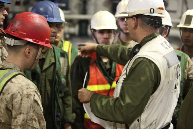 Staff Sgt. Brandon L. Sims, combat cargo well deck assistant, Combat Cargo, Ship's Company, USS Peleliu, briefs his team on the load plan for the well deck of the USS Peleliu before unloading vehicles from a landing craft utility, July 28. Sims, 30, is a native of Livingston, Texas.
