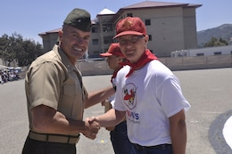 Brig. Gen. Vincent A. Coglianese, commanding general of Marine Corps Installations West - Marine Corps Base Camp Pendleton, shakes hands with Benjamin Hulbert, the 50,000th Devil Pup graduate, during the Devil Pups graduation ceremony on Camp Pendleton's 52 Area Parade Deck, July 28.