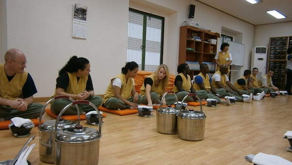 Members of U.S. Forces Korea await their meal during a visit to a Buddhist temple as part of a Korean Cultural Tour July 27-28. The Republic of Korea Ministry of National Defense sponsored the tour designed to introduce USFK service members and their families to Korean history, customs, and traditions. (U.S. Army Photo)