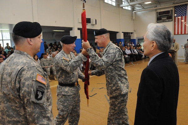 Brig. Gen. Richard L. Stevens (center left), Commander, U.S. Army Corps of Engineers, Pacific Ocean Division, passes the Engineer Colors to Col. Donald E. Degidio, Jr. Far East District incoming Commander, during a ceremony on U.S. Army Garrison Yongsan July 8. Col. Blair A. Schantz (left), outgoing Commander, and Jon Iwata, Deputy District Engineer, look on. (Photo by Patrick Bray)