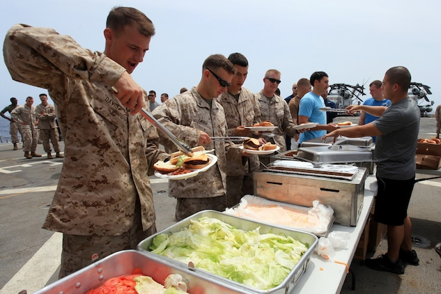 Marines with 24th Marines Expeditionary Unit grab some chow on the flight deck of the USS New York during a steel beach picnic, July 29, 2012, to commemorate the halfway point of their 8-month deployment. The 24th MEU is deployed with the Iwo Jima Amphibious Ready Group as a U.S. Central Command theater reserve force providing support for maritime security operations and theater security cooperation efforts in the U.S. 5th Fleet area of responsibility.