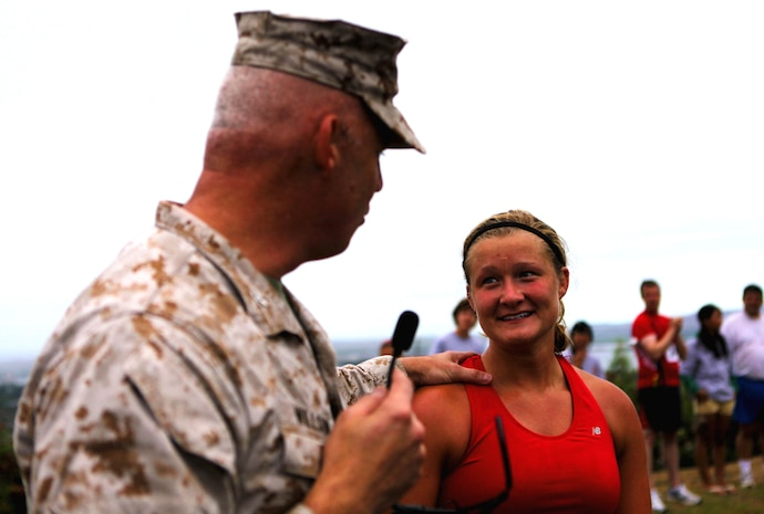 "Col. Brent S. Willson, commanding officer of Headquarters and Service Battalion, U.S. Marine Corps Forces, Pacific, recognizes Moli Copple, from El Paso, Ill., during an award ceremony following the annual Camp Smith 5K Grueler here, July 28. Copple, a basketball player for Millikin University in central Illinois, is on vacation with her family, and ran the race to meet the summer ""5K quota"" set by her team. After being errantly presented with a plaque for one of the fastest female times, Copple immediately returned the award. Willson commended Copple for her integrity and vowed to mail her a souvenir as a token of the battalion's appreciation."