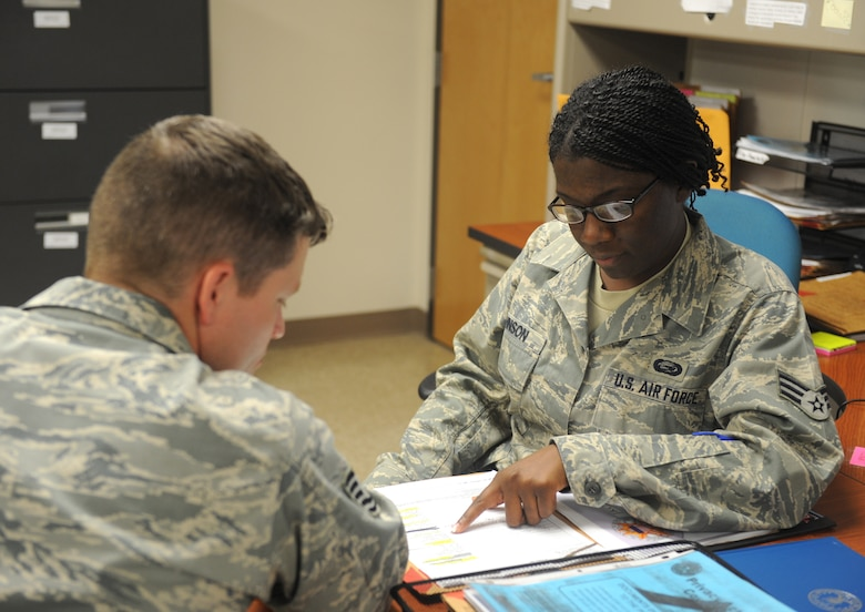 Senior Airman Cedric Johnson (right), 2nd Force Support Squadron military personnel section, goes over paperwork with a customer on Barksdale Air Force Base, La., July 30. Airmen from the MPS assist base personnel who are out-processing by directing them through the various steps of the process. (U.S. Air Force photo/Airman 1st Class Benjamin Gonsier)(RELEASED)