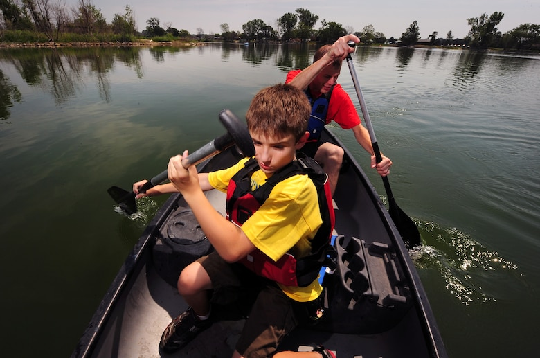 Nine year-old Chris Stewart and Offutt volunteer U.S. Air Force Tech. Sgt. Chris Wroegler navigate their canoe around the Offutt Base Lake during the Exceptional Family Members Program's Camp Offutt July 12 at Offutt AFB, Neb.  This is the second year of the day camp which was founded by Offutt's Exceptional Family Member Program was put on to enhance skills and build friendships.  (U.S. Air Force photo by Josh Plueger/Released)