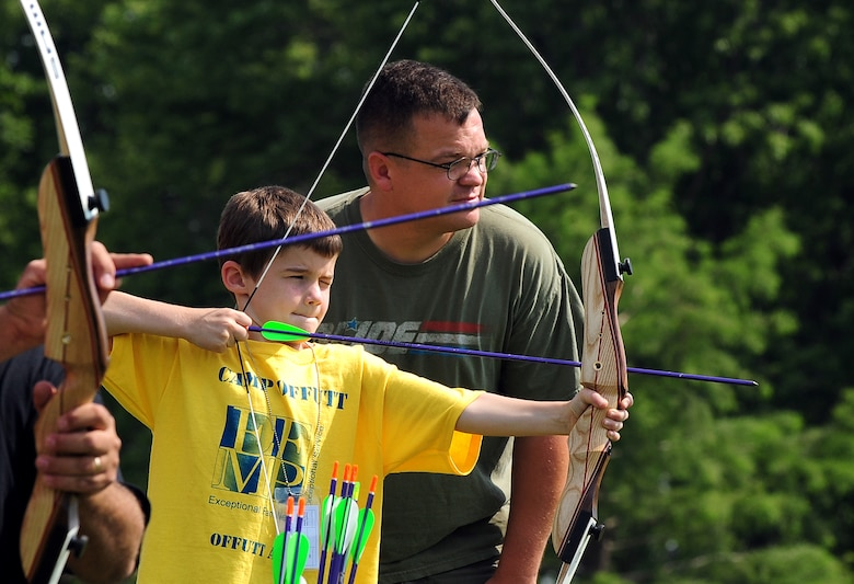 """Eight year-old Michael """"Mikey"""" Holt draws back his bow, with the assistance of U.S. Air Force Staff Sgt. Joseph Unick, a volunteer from Team Offutt, during the Exceptional Family Members Program's Camp Offutt July 12 at Offutt AFB, Neb. The children spend two days at day camp doing several activities designed to enhance confidence and team building skills.  (U.S. Air Force photo by Josh Plueger/Released)"""