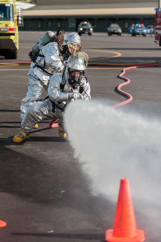 Firefighters  from the 65th Civil Engineer Squadron put out a simulated fire on an aircraft during an joint exercise at Lajes Field, July 30 2012. Lajes Airmen teamed up thier Portuguese counterparts and practiced for a worst case scenario prior to the upcoming Open House on August 5th. (Photo by Lucas Silva)