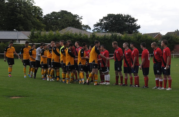 MILDENHALL, England – Players from Mildenhall Town Football Club in the yellow uniforms, shake hands with players from the RAF Mildenhall soccer team before a match July 29, 2012 at the MTFC pitch in Mildenhall. The MTFC won the match with a final score of 14-1. (U.S. Air Force photo/Senior Airman Rachel Waller)