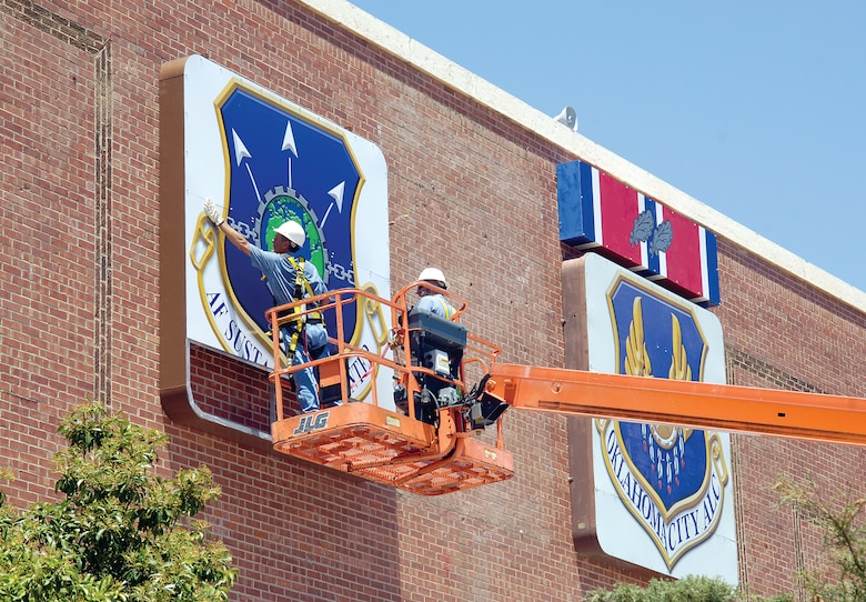 The transformation continues to the face of Bldg. 3001 with the addition of the new Air Force Sustainment Center shield installed July 20. The 72nd Air Base Wing Civil Engineering Directorate's Eddie Boyd, left, and Gregg Garrison shrug off a triple-digit summer day and install the new sign in three sections. (Air Force photo by Margo Wright)