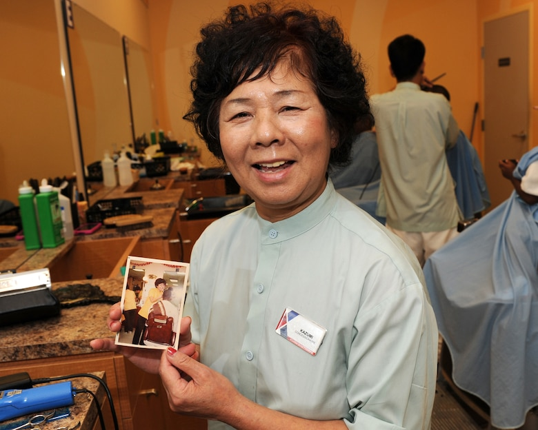 Kazumi Oshiro, Army & Air Force Exchange Service barbershop manager, looks at an old photo taken more than 40 years ago, trimming the hair of a customer on Kadena Air Base, Japan, July 18, 2012. Oshiro has been working at the base barber shop since 1965 and has given an estimated 497,495 haircuts during her 47-year career. (U.S. Air Force photo/Junko Kinjo)
