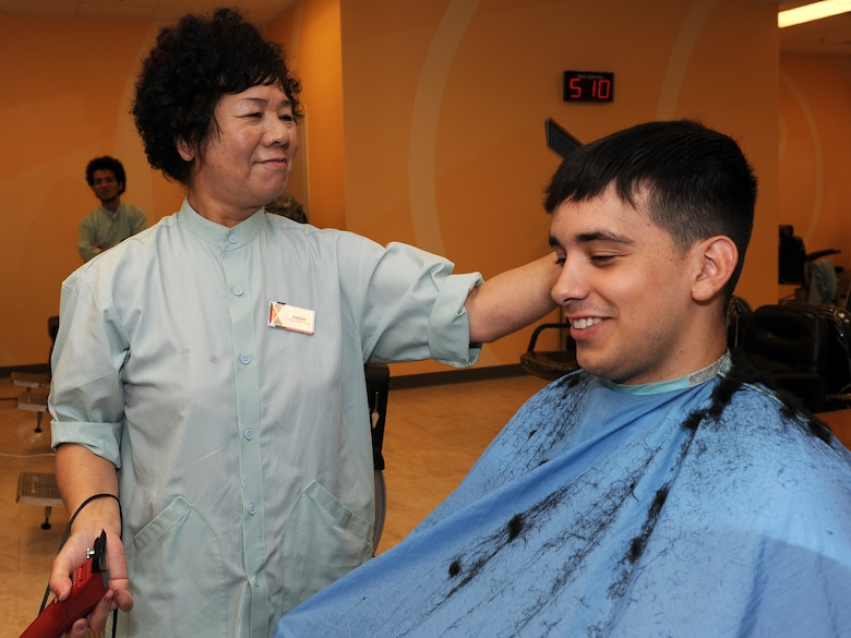 Kazumi Oshiro, Army & Air Force Exchange Service barber shop manager, trims the hair of Airman 1st Class Richard Tato, 18th Component Maintenance Squadron, aerospace propulsions technician, on Kadena Air Base, Japan, July 18, 2012. Oshiro has been working at the base barber shop since 1965 and has trimmed an average of 200 customers per week, or 10,585 customers per year. (U.S. Air Force photo/Junko Kinjo)