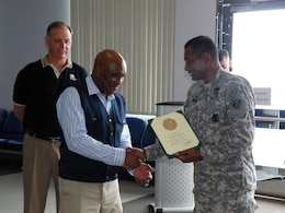Al Mathis, civil engineer and technician at Iwakuni Resident Office, is congratulated for 40 years of service, 34 years with the U.S. Army Corps of Engineers and six years of active military service, by Lt. Gen. Thomas P. Bostick, commanding general, USACE during the general's visit to Marine Corps Air Station, Iwakuni, Japan July 19 as Lee Seeba, Iwakuni program director/resident engineer looks on. (Official USACE photo)