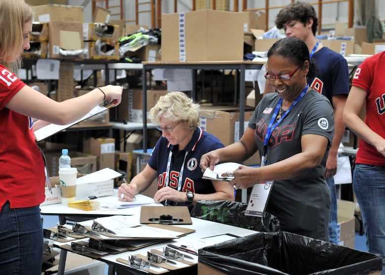 LONDON, England – Angelina Trezel-Vassell, gray shirt, wife of Maurice Vassell, 48th Force Support Squadron, RAF Lakenheath, organizes charts at the USA Olympic team processing center July 25, 2012. More than 300 volunteers from  U.S. Visiting Forces military bases across the United Kingdom signed up to help in preparation for the upcoming 2012 Olympic Games. (U.S. Air Force photo/Senior Airman Jerilyn Quintanilla)
