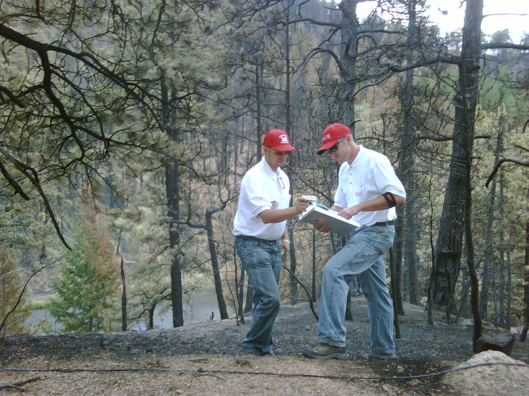 District Civil Engineers Carlos Aragon (left) and John Stages deployed to a forested area near Colorado Springs, Colo., in mid-July to perform a flood risk assessment following the devastating Waldo Canyon Fire.
