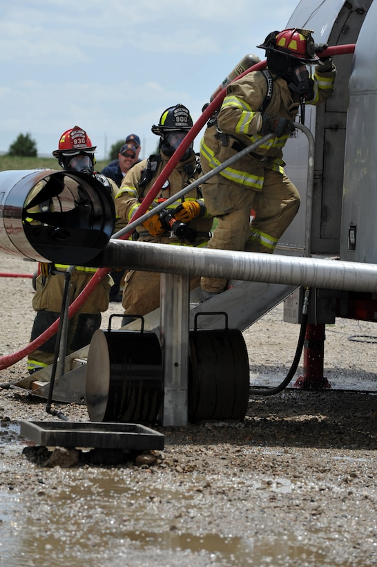 BUCKLEY AIR FORCE BASE, Colo. -- Aurora firefighters enter a mobile air fire trainer to during an exercise May 30, 2012. (U.S. Air Force photo by Airman 1st Class Darryl Bolden Jr.)