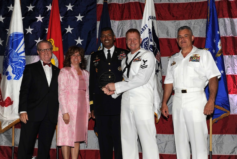 Peter Wertimer, Charleston Chamber of Military Policy council chairman, Julie Gerthoffer, Charleston Chamber of Military Relations Committee and U.S. Army Lt. Gen. Vincent Brooks, Third Army commanding general, present Petty Officer Jonathan Pitts, a Mineman and Leading Petty Officer Magazine/Field Crew, the'Enlisted Service Person of the Year' award, alongside his commanding officer, CDR Charles Phillip, Naval Munitons Command commander, during 'Salute to the Military' May 23, 2012 at the North Charleston Convention Center, S.C. This is the eighth year the Charleston Metro Chamber of Commerce recognized the local active-duty, reserve, and civilian personnel for their community service above and beyond their call of duty. (U.S. Air Force photo/Airman 1st Class Ashlee Galloway)