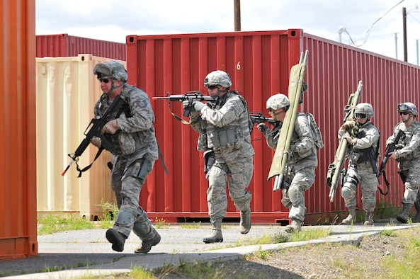 Members of the 141st Security Forces Squadron return fire while advancing to injured personnel during a simulated aircraft incident at Fairchild Air Force Base, Wash., June 2, 2012. 141st SFS members participated in several different training scenarios during the simulated peace-keeping mission. (U.S. Air Force photo by Staff Sgt. Anthony Ennamorato/Released)