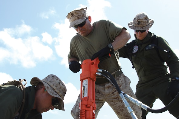 WEST FIELD, Tinian-Lt. Col. Thomas E. Frederick, center, mans a jackhammer with Sgt. Joseph R. Pachco, left, and Lance Cpl. Devin J. Ward at Tinian's West Field, May 18th, during Exercise Geiger Fury 2012. The Marines use the jackhammer to drive M-31 arresting gear stakes into the runway at the field. Frederick is the executive officer of Marine Aircraft Group 12, 1st Marine Aircraft Wing, III Marine Expeditionary Force. Pachco and Ward are expeditionary airfield technicians with Marine Wing Support Squadron 171, MAG-12, 1st MAW, III MEF. (U.S. Marine Corps photo/Lance Cpl. Gage Karwick/Released)