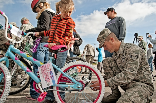 Senior Airman Christopher Christman, 124th Logistics Readiness Squadron, helps a child with her new bike provided by the Burgers for Bikes, Bikes for Kids program, May 5, at Applebee's Restaurant on Vista Avenue in Boise. For 20 years, Idaho Air National Guard volunteers have transported and provided on-site repairs and adjustments to more than 5,250 bikes for deserving youth who are nominated through local schools. (Air Force photo by Tech. Sgt. Becky Vanshur)