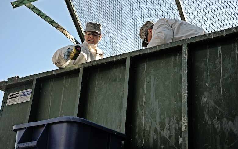 Senior Airman Heidi Caye, environmental protection specialist for the 124th Civil Engineer Squadron otsses an aluminum can she found in the trash into a blue recycling receptacle Feb. 28 at Gowen Field in Boise, Idaho. She and Master Sgt. Robert McGarvie, bioenvionrmental engineer from the 124th Medical Group, began the process of evaluating the wing's recycling program by sifting through trash dumpsters to determine what percentage of trash airmen throw away is actually recyclable.