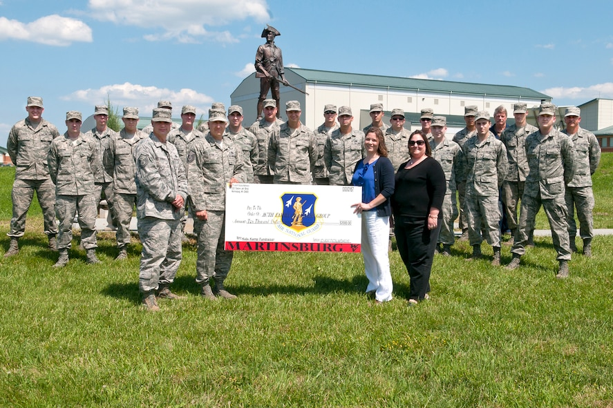 Master Sgt. Kevin Goulet and Master Sgt. Bradly Teter, both from the 167th Aircraft Structural Maintenance Shop, presented Christy Miller, 167th Family Readiness President, and Sherry Lewis, manager of the 167th Airman and Family Readiness Program, with a check for $2000 to be used as scholarship money for the West Virginia National Guard's Kids Kamp and Youth Leaders Camp held in Camp Dawson, W.Va., at the end of June. Other members of the Structural Maintenance Shop, involved with the fundraising efforts, stand behind. (Air National Guard photo by Airman 1st Class Nathanial Taylor)
