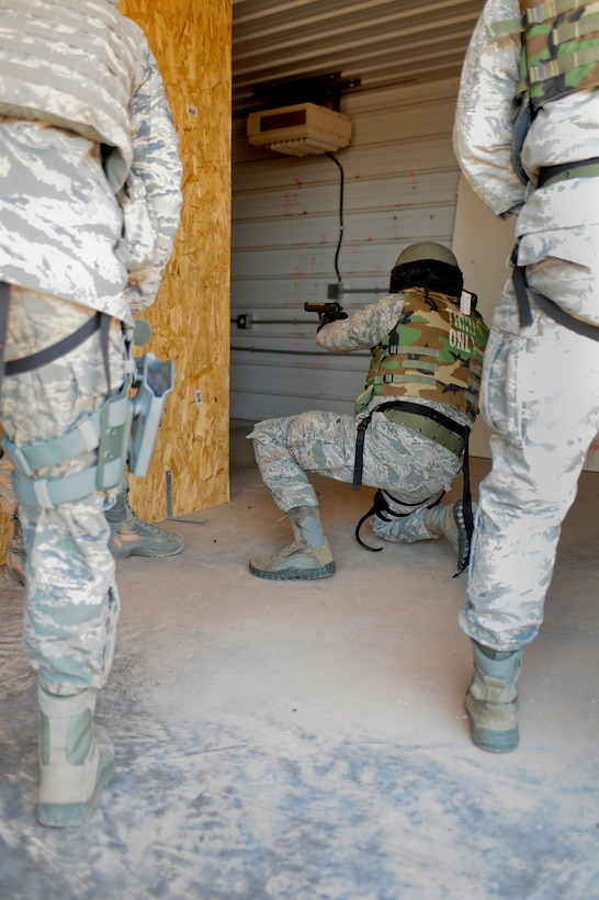 U.S. Air Force Col. Buck Elton, 27th Special Operations Wing commander, kneels down while aiming his weapon at the combat arms shoot house at Cannon Air Force Base, N.M., May 29, 2012. Members of the 27th Special Operations Security Forces Squadron Deployed Aircraft Ground Response Element Team use Cannon's combat arms shoot house  by to aid in refining skills such as dealing with multiple targets, identifying shoot or no-shoot situations and switching from primary to secondary weapons. (U.S. Air Force photo by Airman 1st Class Eboni Reece)