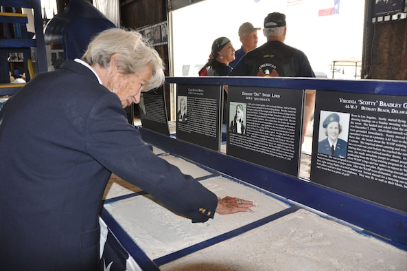 "SWEETWATER, Texas -- WASP Dorothy ""Dot"" Swain Lewis reminisces as she places her hand in a concrete mold of her handprints inside the Avenger Field hangar May 26. Lewis was a primary instructor at Avenger Field before joining the WASP program as a trainee. Upon graduation, she was stationed at Columbus Army Air Field, Miss.,and Laredo Army Air Base, Texas, flying AT-10s, P-40s, P-63s and B-26s. (U.S. Air Force photo/Maj. Jessica Martin)"