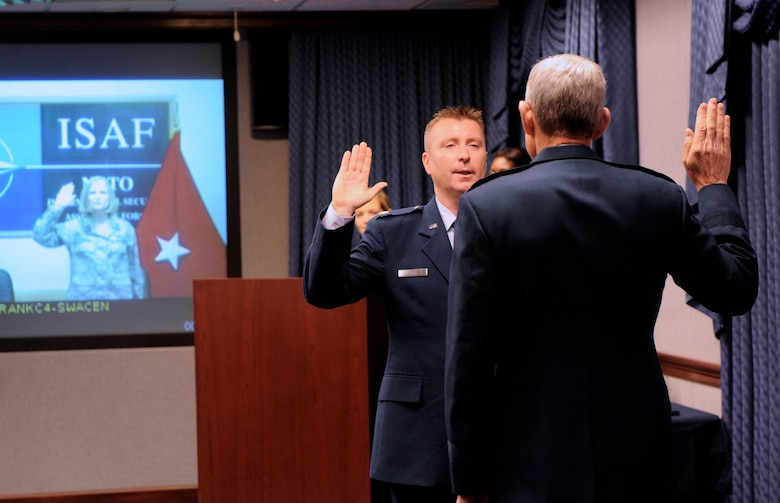 Air Force Chief of Staff Gen. Norton Schwartz administers the oath of office to Maj. Lori Hodge and her husband, Maj. Christian Hodge, during a unique promotion ceremony at the Pentagon in Washington, D.C., June 4, 2012.  Christian attended the ceremony in person while Lori, who is deployed to Kabul, Afghanistan, attended via video teleconference.  The two were promoted from captain to the rank of major during the ceremony.  (U.S. Air Force photo/Andy Morataya)