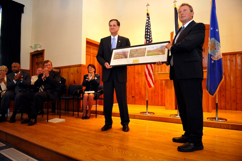 DENVER, Colo. -- Denver and Air Force Personnel Center leaders watch as a lithograph is presented to Montgomery Force, Lowry Redevelopment Authority executive director, right, by Stephen TerMaath, Base Realignment and Closure Program Management division chief, May 31, 2012. The presentation marked the turn-over of the Buckley Annex, the last 70-acres of the former Lowry Air Force Base, to the city of Denver. (U.S. Air Force photo by Staff Sgt. Kathrine McDowell)