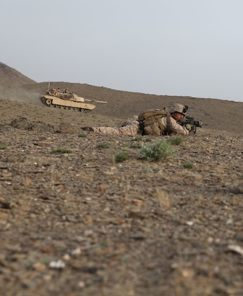 A tank drives by to provide better security for the Marines with Charlie Company, 1st Battalion, 8th Marine Regiment, as they prepare to search a village for Taliban fighters in the early morning, April 18, 2012. The Marines and sailors with Charlie Co. took part in a month long operation where they cleared the Gostan valley of enemy forces.