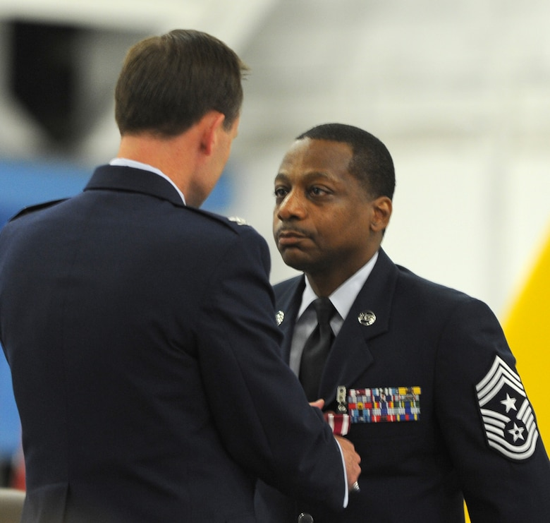 Colonel Ken Rizer, 11th Wing/Joint Base Andrews commander, presents Chief Master Sgt. Anthony Brinkley, 11th Wing/Joint Base Andrews command chief, with a medal during Brinkley's retirement ceremony June 8, 2012.  Brinkley served more than 28 years in the Air Force.  (U.S. Air Force Photo by Staff Sgt. Torey Griffith)