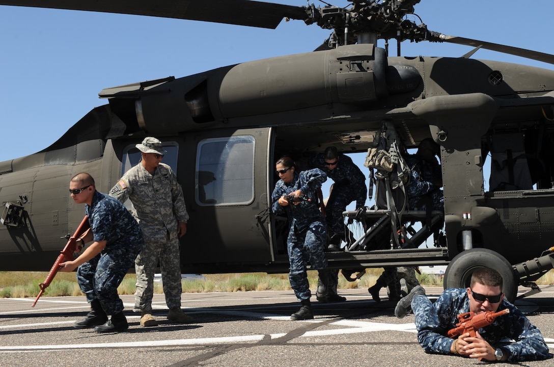 Members of the U.S. Navy learn how provide cover for a UH-60 Black Hawk during helicopter pre-deployment training at Davis-Monthan Air Force Base, Ariz. June 7. This training was to prepare Airmen, Marines, soldiers and sailors for actions they might experience in combat. (U.S. Air Force photo by Senior Airman Brittany Dowdle/released)