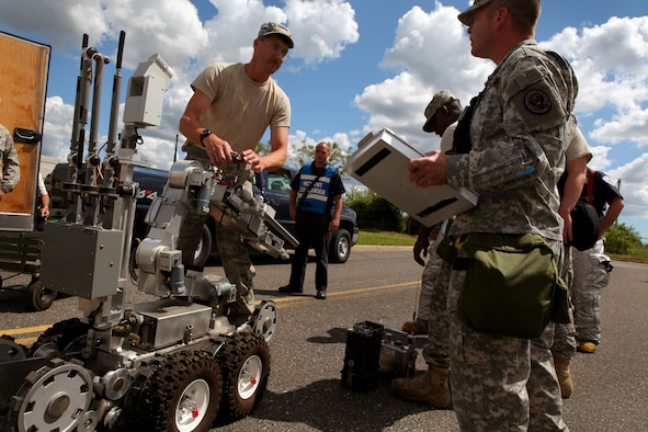 Explosive Ordnance Disposal non-commissioned officer in charge Master Sgt. Ed Nickel, left, pauses while loading an ANDROS F6A Explosive Ordnance Disposal robot to answer a question from Maj. Scott Hofstetter, deputy commander, 21st Civil Support Team (Weapons of Mass Destruction), New Jersey National Guard, during an exercise at the 177th Fighter Wing June 6, 2012. Airmen from the 177th along with New Jersey National Guard Soldiers and Airmen of the 21st Civil Support Team (Weapons of Mass Destruction), South Jersey Transit Authority firefighters and New Jersey State Police responded to a simulated weapons of mass destruction incident.  Members of the 177th Explosive Ordnance Disposal team worked with the 21st CST in reacting to a simulated explosion on base. The 21st CST supports civil authorities by responding to a weapons of mass destruction (WMD) situation. The unit is made up of full-time New Jersey Army and Air National Guard members that have been trained and equipped to provide support to civil authorities at a domestic chemical, biological, radiological, nuclear and high-explosive (CBRNE) incident site by identifying CBRNE agents/substances, assessing current and projected consequences and advising on response measures and assisting with appropriate requests for state support.  U.S. Air Force photo by Master Sgt. Mark C. Olsen