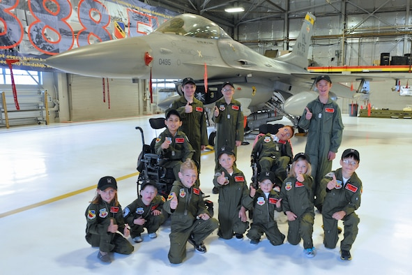 Kids and pilots from the 388th Fighter Wing gather May 25 at an event organized by the 421st Fighter Squadron and the Make-A-Wish Foundation to let children learn what it's like to be a fighter pilot at Hill Air Force Base. (U.S. Air Force photo by Kim Cook/Released)