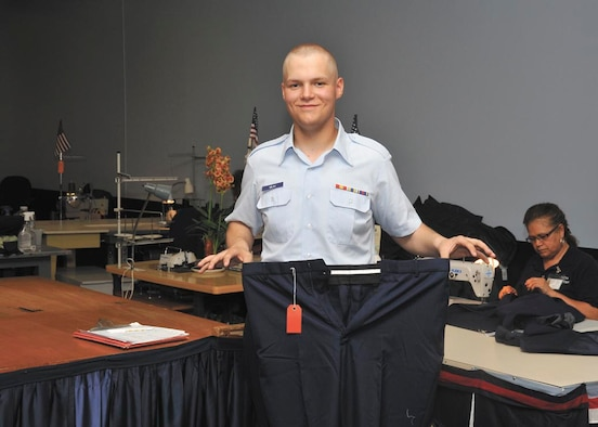 Airman Mitchell Imlah holds size 41 trousers, the largest available at basic training May 18 at the clothing issue facility. Now wearing a size 32, at one time, Imlah wore size 46 trousers before losing weight and joining the Air Force. (U.S. Air Force photo/Alan Boedeker)