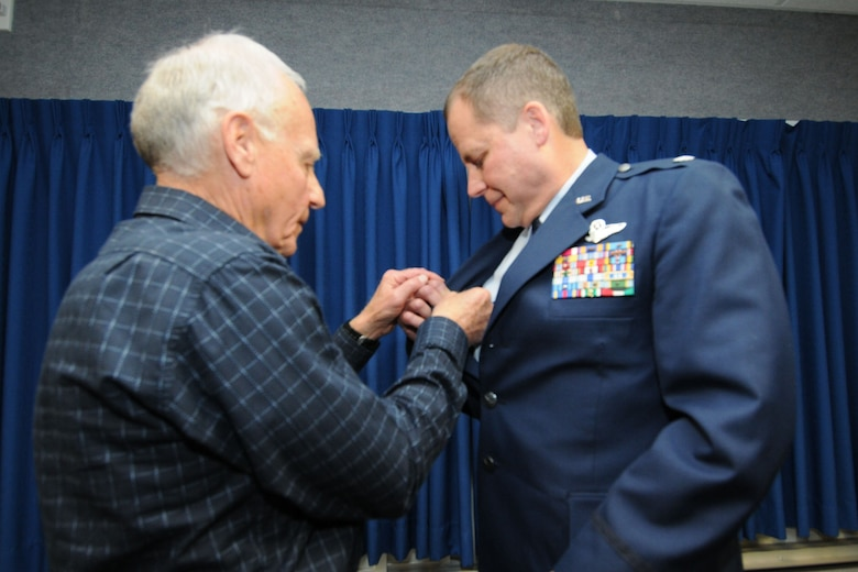 JOINT BASE ELMENDORF-RICHARDSON, Alaska - Retired U.S. Air Force Col. Joseph Coniglio fastens on a command pin to the lapel of his son's, Lt. Col. Scott Coniglio, June 6, 2012. A command pin worn above the name tag signifies that the person wearing the pin above the nametag is a current commander. Lt. Col. Coniglio is the new commander of the 176 Maintenance Group. He will be in charge of more than 200 Airmen responsible for the maintenance of 176 Wing's airplanes and helicopters. National Guard Photo by Tech. Sgt. Jennifer Theulen.