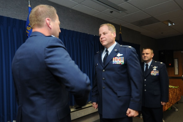 JOINT BASE ELMENDORF-RICHARDSON, Alaska - Lt. Col. Scott Coniglio accepts command of the 176 Maintenance Squadron from Col. Mark Hedlund, 176 Maintenance Group commander after Col. Michael Griesbaum relinquished command of the squadron June 6, 2012. Coniglio will be in charge of more than 200 Airmen responsible for the maintenance of the fixed-wing aircraft and helicopters. National Guard Photo by Tech. Sgt. Jennifer Theulen.