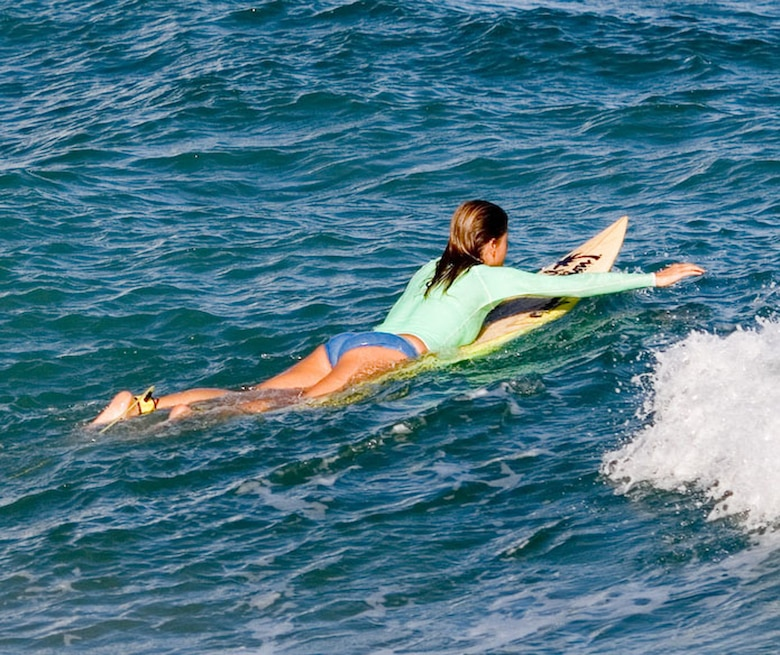 Lying prone on a surfboard can cause hyperextension of the spine and lead to a rare injury called surfer myelopathy. Symptoms include back pain, tingling sensation in the legs, loss of feeling in the legs, inability to walk, paralysis and urinary retention. (Photo by Kanaka Menehune)