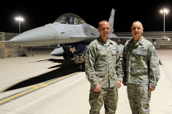 Staff Sgt. Corey Revels, an avionics technician assigned to the 451st Expeditionary Aircraft Maintenance Squadron and his father, Senior Master Sgt. James Revels, Jr., superintendent for the 451st Expeditionary Maintenance squadron, pose for a photo in front of an F-16 Fighting Falcon May 31, 2012. Personnel are deployed from McEntire Joint National Guard Base, S.C., in support of Operation Enduring Freedom. Swamp Fox F-16?s, pilots, and support personnel began their Air Expeditionary Force deployment early April to take over flying missions for the air tasking order and provide close air support for troops on the ground in Afghanistan.