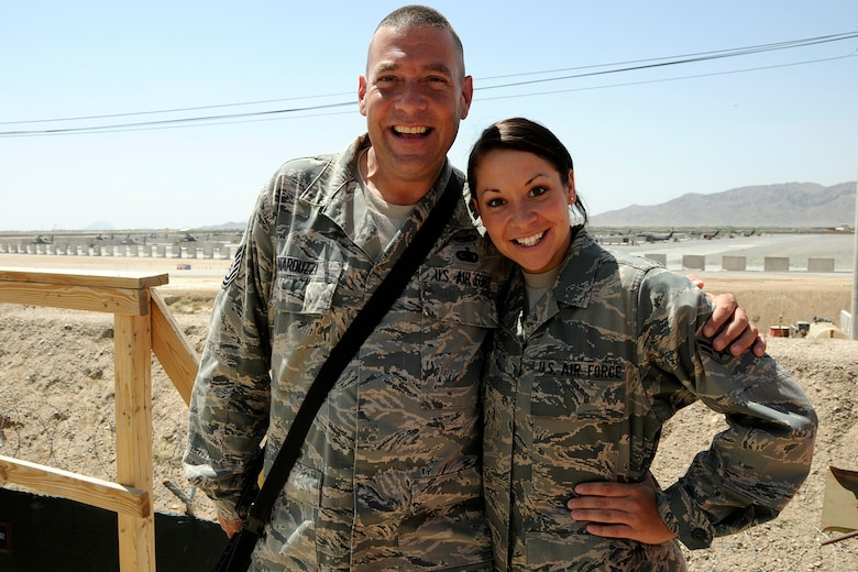 Technical Sgt. Douglass Narduzzi, a maintenance operations controller assigned to the 451st Expeditionary Maintenance Group and his daughter Airman 1st Class Lauren Narduzzi, an aircrew flight equipment technician assigned to the 157th Expeditionary Fighter Squadron at Kandahar Airfield Afghanistan, pose for a photo 12 May, 2012. Personnel are deployed from McEntire Joint National Guard Base, S.C., in support of Operation Enduring Freedom. Swamp Fox F-16's, pilots, and support personnel began their Air Expeditionary Force deployment early April to take over flying missions for the air tasking order and provide close air support for troops on the ground in Afghanistan.