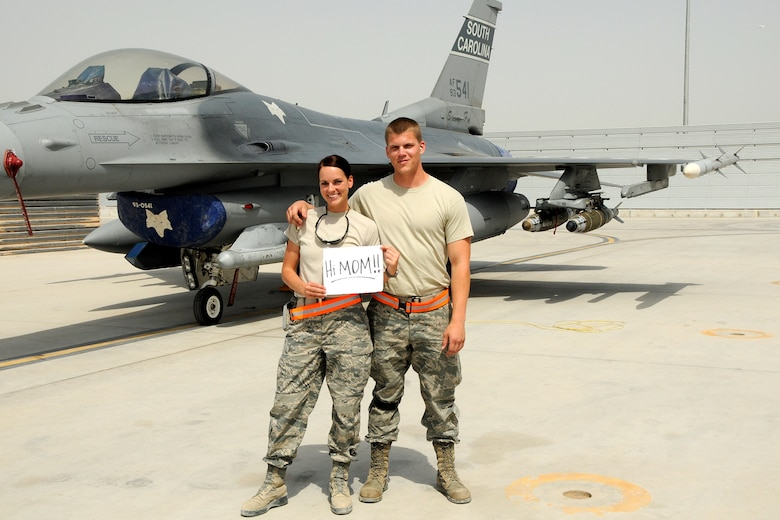 Technical Sgt. Caycee Cook, a public affairs photographer assigned to the 157th Expeditionary Fighter Squadron and her brother Senior Airman Chance Watson, an avionics technician assigned to the 451st Expeditionary Aircraft Maintenance Squadron at Kandahar Airfield, Afghanistan, pose for a photo in front of an F-16 Fighting Falcon May 10, 2012. Personnel are deployed from McEntire Joint National Guard Base, S.C., in support of Operation Enduring Freedom. Swamp Fox F-16's, pilots, and support personnel began their Air Expeditionary Force deployment early April to take over flying missions for the air tasking order and provide close air support for troops on the ground in Afghanistan. (U.S. Air Force photo/MSgt. Chris Smoak)