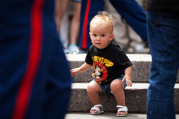 Lucia Abec, granddaughter of Vietnam War veteran Marine Sgt. Roland Briceno, looks up from climbing the stairs amidst a sea of Marine dress blue delta trousers following the Proclamation Ceremony for Marine Week Cleveland June 11, 2012. Briceno, who served four years active duty and two years reserve, brought his daughter and four granddaughters from Toledo, Ohio, to enjoy the opening day of Marine Week events. More than 750 Marines will be in Cleveland June 11-17 displaying Marine aircraft, vehicles and equipment, as well as interacting with and educating the public on the values and character of the Marine Corps. One of the culminating events will be a Marine Air Ground Task Force demonstration, which showcases Marines' ability to assault from ship-to-shore via ground and air, June 16-17 at Burke Lakefront Airport.