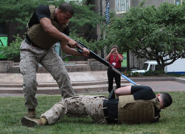 A passerby stops to snap photos as instructor trainer Staff Sgt. Shurron Thompson, a Coatesville, Penn., native, demonstrates bayonet and rifle submission techniques on fellow instructor trainer Staff Sgt. John Badon, ground, a Lufkin, Texas, native, during a Marine Corps Martial Arts Program demonstration in Public Square June 12 during Marine Week Cleveland. Program demonstrations are scheduled to continue Wednesday through Friday at 10 a.m. and 3 p.m. during Marine Week.