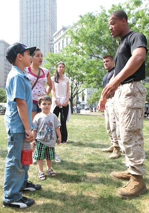 Crystal Rudyak and her sons Alex, 8, and Anthony, 2, discuss martial arts with instructor trainer Staff Sgt. Shurron Thompson, a Coatesville, Penn., native, following a Marine Corps Martial Arts Program demonstration June 12 during Marine Week Cleveland. The Rudyaks traveled from Parma to catch a glimpse of what can be achieved through years of martial arts training. Marine Week Cleveland is scheduled to continue through June 17.
