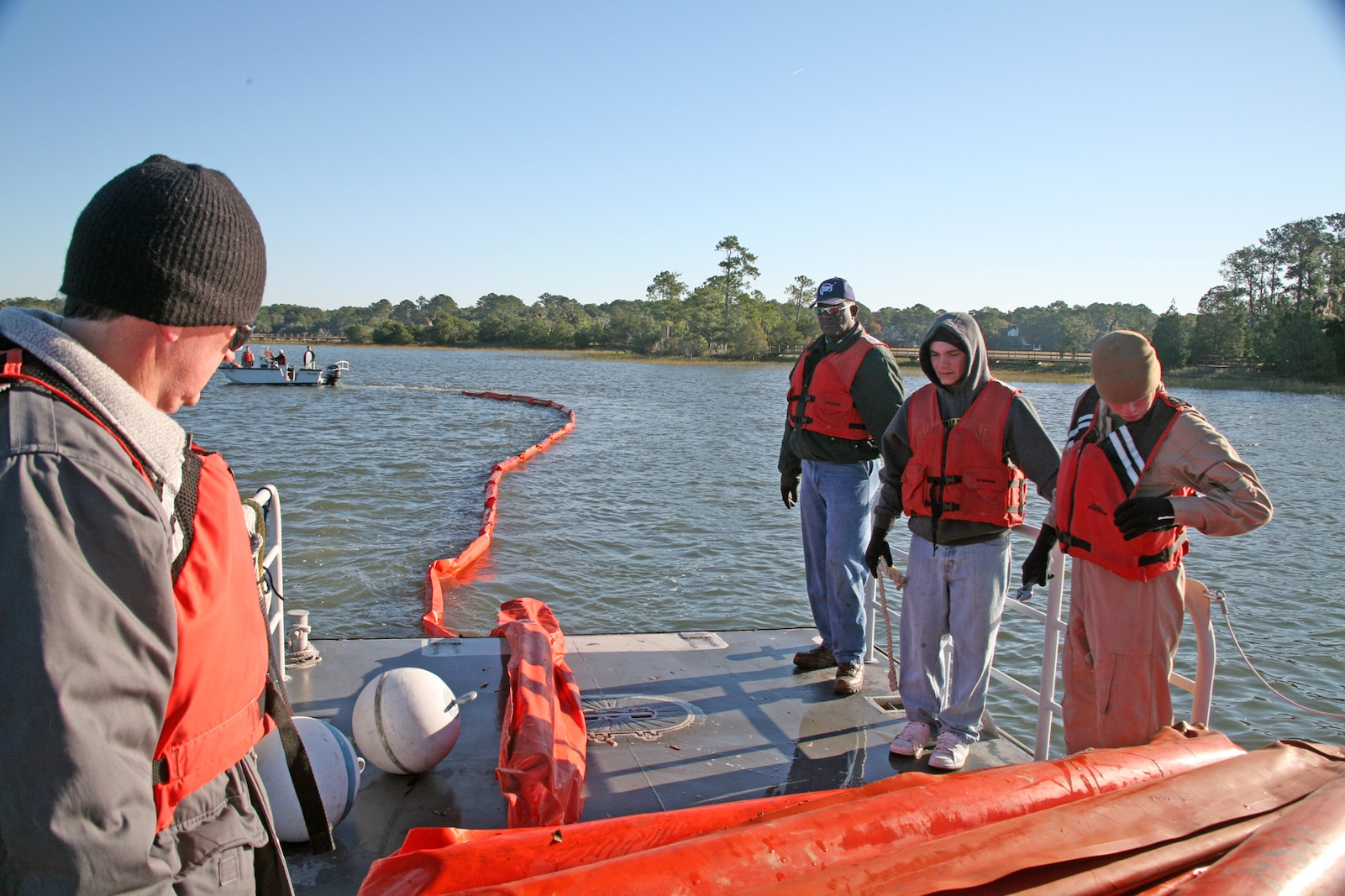 MARINE CORPS AIR STATION BEAUFORT, S.C. - Members of the Facility Response Team observe the booms being towed out to the water to ensure there are no tangles during a simulated oil spill training exercise Oct. 29, at the station's fuel pier.