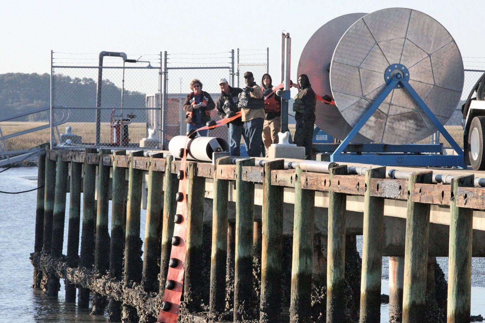MARINE CORPS AIR STATION BEAUFORT, S.C. - Members of the spill management team deploy a hard boom into the water at the Air Station fuel pier Nov. 2. The spill management team and facility response team work together to capture hazardous material in water.